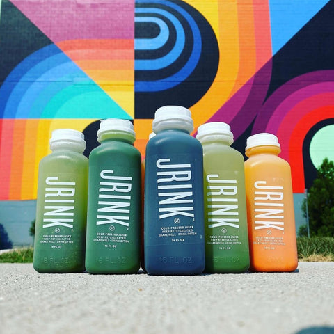 5 cold pressed juices lined up in a row
