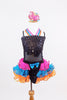 Black sequined &mesh leotard has crystal bow/band accents. Has colourful triple halter straps, pink-turquoise-orange organza ruffled skirt &matching headpiece. Front