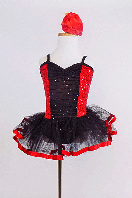 Red sequin leotard  has center panel of black ruffles. Comes with black  tulle skirt with red satin edge, black gauntlets & red satin floral hair accessory. Front