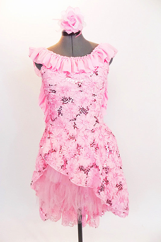 Pink leotard dress has pink sequined, floral lace overlay & high-low skirt . The scoop neck and low  back are has pink crepe ruffle.& matching hair accessory. Front