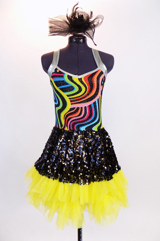 Rainbow swirled patterned leotard with yellow bottom and silver straps, has an attached skirt of ruffled, layered yellow tulle with a black sequined overlay. Front