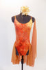 Burnt orange camisole leotard has a tie-dye effect with gold leaf pattering, scalloped low back with straps & an attached chiffon skirt. Has hair piece & scarf. Front