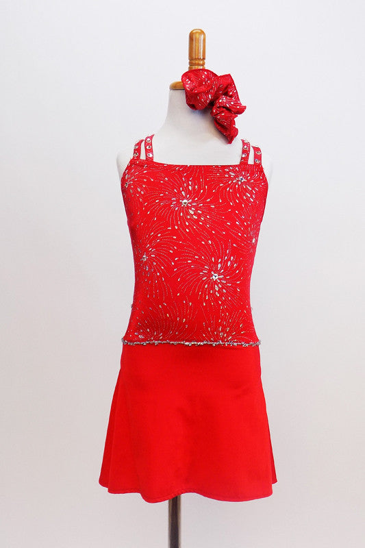Red camisole style leotard dress has silver firework motif with crystal centers & straps that criss-cross around crystal ring on back. Has matching hair piece. Front