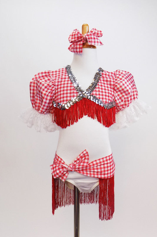 White leotard has red-white checkered bust area,  pouf sleeves with lace,  silver sequins and red fringe. Has checkered hip wrap with red fringe & hair bow. Front