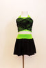Neon green halter half-top has front cross over black mesh accent. It comes with a black skirt that has attached bottom and matching green waistband. Front