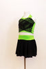 Neon green halter half-top has front cross over black mesh accent. It comes with a black skirt that has attached bottom and matching green waistband.  Side
