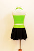 Neon green halter half-top has front cross over black mesh accent. It comes with a black skirt that has attached bottom and matching green waistband.  Back