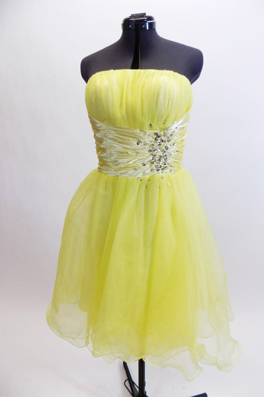Layers of fluffy, soft yellow tulle with curly edges, form the skirt portion of this knee length dress. The waistband is ruched satin with crystals and sequins. Front