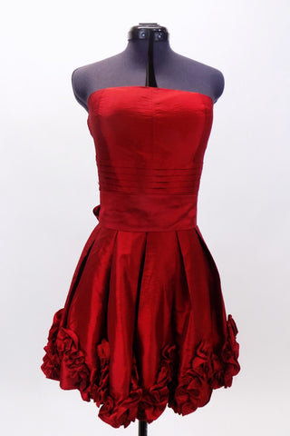 Red strapless taffeta dress has pleated front waist band & smocked back. Bottom of the dress is scalloped with rosettes.Has wide sash that  ties at the back. Front zoom