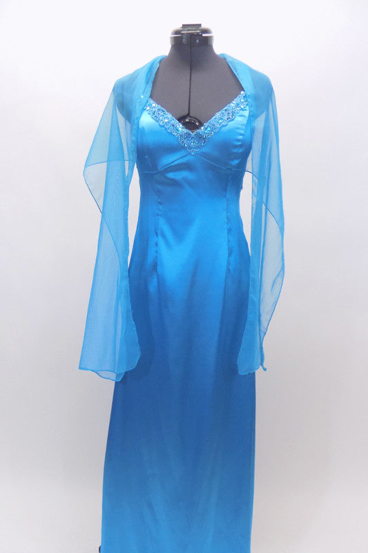Floor length satin turquoise gown has jeweled trim at bust. The straps from the shoulder and bottom of bust line cross over at back. Has long chiffon train. Front with shawl