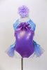 Lavender  and aqua leotard has tulle bustle skirt. Bodice is accented with lavender beads &  large purple sequined flower. Has is a large flower hair accessory. Front