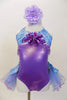 Lavender  and aqua leotard has tulle bustle skirt. Bodice is accented with lavender beads &  large purple sequined flower. Has is a large flower hair accessory Front