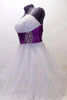 White curly edge tulle boned dress has ruched purple satin waist band with large jewel accents. There is scattered amethyst Swarovski crystals throughout dress. Side