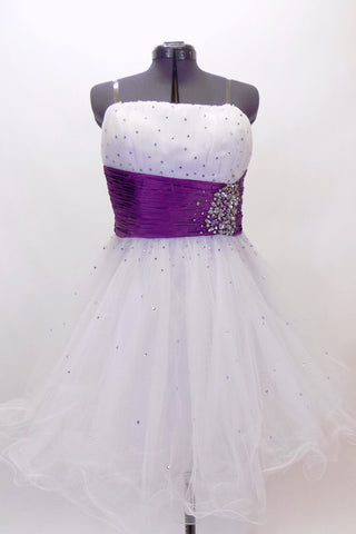 White curly edge tulle boned dress has ruched purple satin waist band with large jewel accents. There is scattered amethyst Swarovski crystals throughout dress. Front