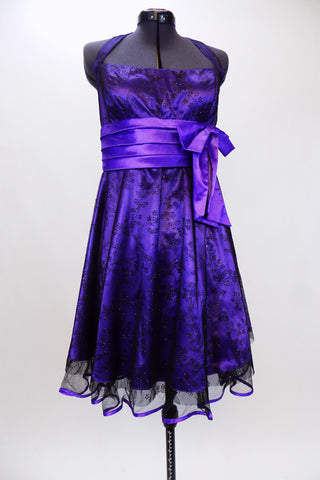 Purple halter  A-line knee length dress has black lace overlay & purple satin piping on petticoat. Has wide pleated  waistband with large satin bow under bust. Front