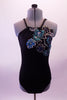 Black leotard has a halter style neckline with a braided cord that unravels to become tree back straps on either side forming a criss-cross pattern along the low open back. Along the front left & side is a gorgeous large beaded, sequined & fully crystalled applique of cascading flowers in shades of blues & greens. Front