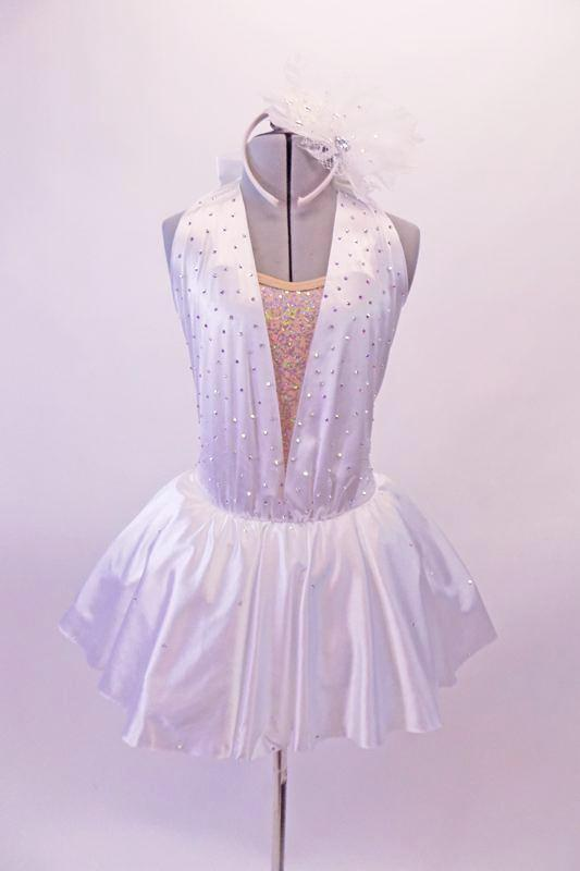 White satin dress is covered in crystals. The nude sequined front has a shawl collar of white that extends from the waist of the skirt and attaches at the back with a bow accent. The shirt has a crinoline/tulle petticoat for added volume and is covered in scattered crystals. Comes with white fascinator headband. Front
