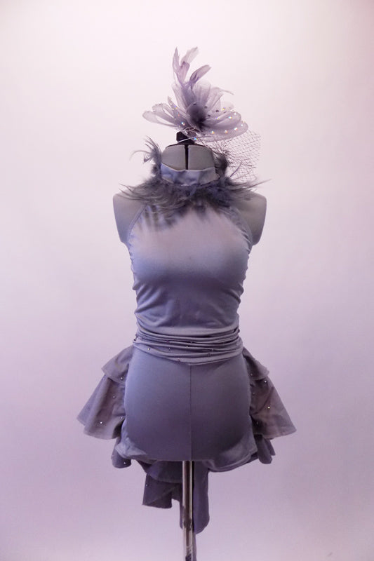 Halter style silver-grey silver unitard with ruched waist has feather accents lining the collar. The wide T-back give the costume a unique flare & good support. Attached is a high low-style layered bustle skirt in canvas-type cotton adorned with small crystals throughout. Comes with a large crystal-accented hairband. Front