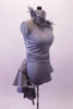 Halter style silver-grey silver unitard with ruched waist has feather accents lining the collar. The wide T-back give the costume a unique flare & good support. Attached is a high low-style layered bustle skirt in canvas-type cotton adorned with small crystals throughout. Comes with a large crystal-accented hairband. Right side