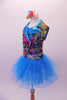 Colourful costume has a turquoise tulle skirt with rainbow sequin waistband, attached to a turquoise short unitard base. The brightly coloured graffiti-style vest has shiny blue lapels with wide rainbow sequin accent. Comes with matching gauntlets and hair accessory. Left side