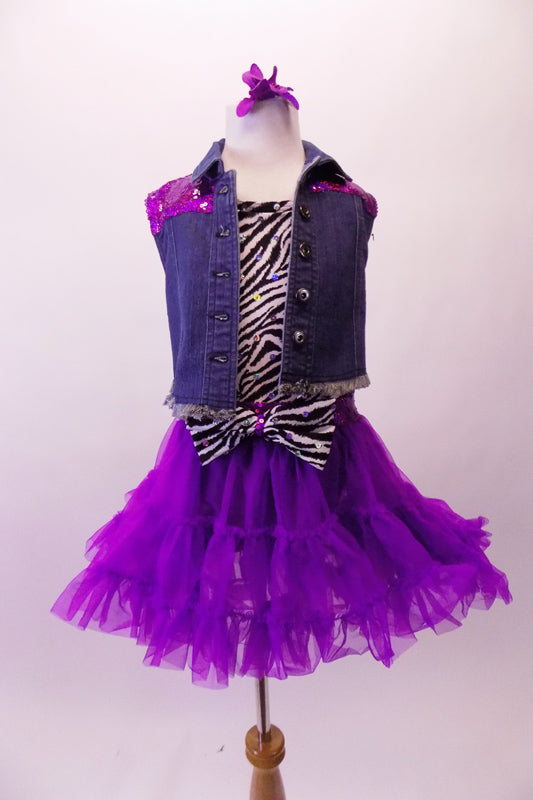 Zebra print short unitard with black bottom comes with a purple ruffled pull-on layer skirt with sequined waistband and large zebra bow accent at the front. A denim vest with purple sequined back accompanies the outfit. Comes with zebra stirrup socks, flower hair accessory and purple sequined gauntlets. Front