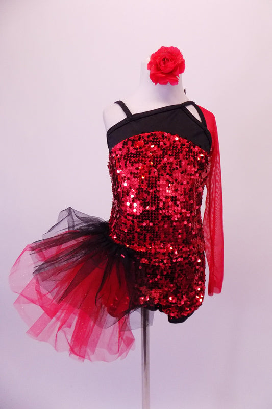 Red sequined short unitard has a black bust area angle & strapped in a unique angle with single red mesh long sleeve. The deep open back has three angled straps with a large sequined red and black floral accent. A large red and black tulle side pouffe accents the right hip. Comes with a red floral hair accessory. Front