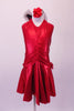 Red, metallic, knee-length dress is gathered along the front centre of the bodice. The halter collar has a large red and black bow at the back of the neck. The dress has a jewelled accent at the left hip and comes with a red floral hair accessory. Front