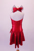 Red, metallic, knee-length dress is gathered along the front centre of the bodice. The halter collar has a large red and black bow at the back of the neck. The dress has a jewelled accent at the left hip and comes with a red floral hair accessory. Back