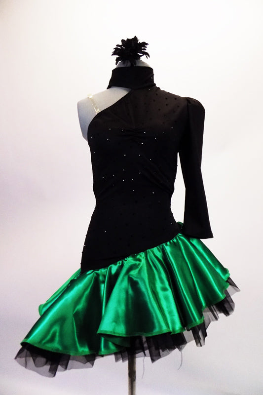 Dress has a black torso with a single shoulder and long left pouffe sleeve, attached to a neckband collar. The entire torso is covered with SS20 black crystals and is angled down towards the right hip. The emerald satin skirt had layered black ruffled petticoat for added volume. Comes with a hair accessory. Front