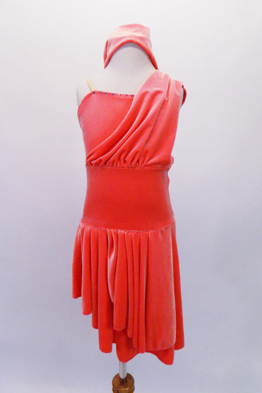 Salmon coloured velvet high-low dress has clear shoulder straps and a gathered front drape that extends just over the left bust to the shoulder. Crystals accent the bustline for a little sparkle. Comes with separate matching briefs and headband. Front