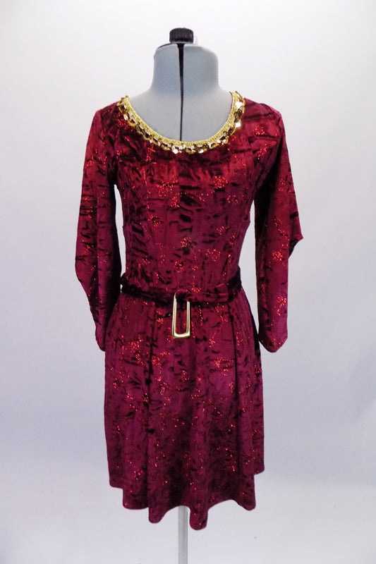 Burgundy crushed velvet, A-line tunic dress has glitter floral detail in the fabric and gold sequined braid that sits along the neckline. The ¾ angel-sleeve gives the dress a medieval look. Comes with tie belt and hair accessory. Front