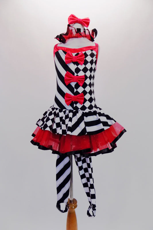 Harlequin themed tutu dress is an alternating pattern of black-white stripes & black-white checks. A red tulle skirt with black satin ribbon makes the skirt & matches the ruffled collar. Three red bows accent the bodice. Comes with red hair bow & stirrup socks. Front