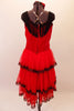 Saloon girl themed, knee-length dress has layers of red, lace-trimmed sheer skirt attached to a red velvet bodice. Black fringe adorns the shoulders and extends along the back Comes with crystalled rose hair accessory. Back
