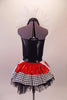 Halter style leotard dress has a large red heart front over a back base with ruffled organza collar. The attached skirt is shiny red with a black & white houndstooth edge over the top of black tulle. Two large white & red heart panels accent each of the hips. Comes with a mini black top hat with a heart accent.  Back