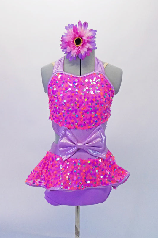 Pink and lavender costume is covered in pink sequins that give way to a peplum skirt that is short at the front revealing the lilac brief beneath. The peplum extends lower at the back with a bow that matches the one at the front torso. Comes with a floral hair accessory.  Front