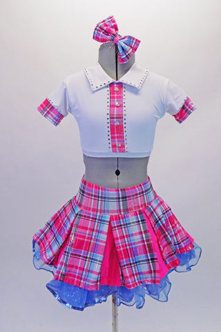 School uniform themed  2-piece costume comes with a wide pleated pink & blue tartan skirt with a wide waistband & bright pink inner pleats. The matching white half top has collar, buttons & cap sleeves with AB crystals and tartan accents. Comes with a large tartan bow hair accessory & purple gauntlets. Front