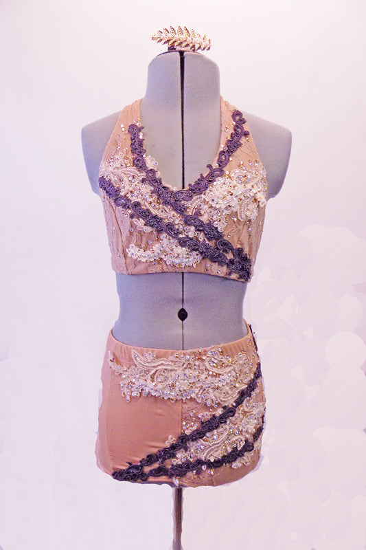 Nude based 2-piece costume has a halter neck bra top and brief style shorts. White breaded and crystalled bridal applique adorns both top and bottom which are further accented with narrow, angled bands of embroidered lace applique in a purple/grey hue. Comes with hair barrette. Front