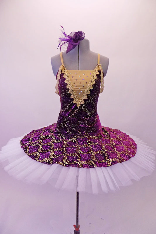 Tutu has a deep purple velvet base with gold brocade design. The bodice has a lined, nude V-front bust area with crystal accents & gold crochet lace edging that extends to form draping shoulder loops. The back has cross straps for support. The overlay skirt with attached basque sits over top of the white pull-on tutu. Front