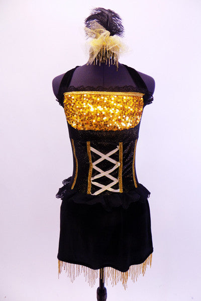 Halter style leotard dress has gold sequined bust area with ruffle. Bodice is corset style & black skirt has gold bead fringe. Comes with feather hair accessory. Front