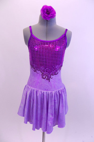 Pale lavender marble  leotard dress has purple glitter front bodice and low open back with cross straps.  A purple glitter swirled applique accent surrounds the glittery bodice. Comes with matching hair accessory. Front
