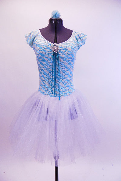 Knit stretch lace covers an aqua base on this two tone leotard tutu dress with ruffle cap sleeves. The front and back are scoop neck with a front crystal broach and ribbon accent. The attached tutu skirt is comprised of several  layers of white crystal tulle. Comes with matching hair accessory. Front