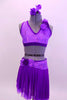 Two piece costume comes with purple sequined lace halter half top. The back has crystal covered straps with crystal ring accent.  The skirt has layers of darker purple mesh with lighter matching lace accent around hip. Both pieces have lace rose accents on left shoulder and right hip. Comes with floral hair accessory. Front