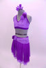Two piece costume comes with purple sequined lace halter half top. The back has crystal covered straps with crystal ring accent.  The skirt has layers of darker purple mesh with lighter matching lace accent around hip. Both pieces have lace rose accents on left shoulder and right hip. Comes with floral hair accessory. Left side.