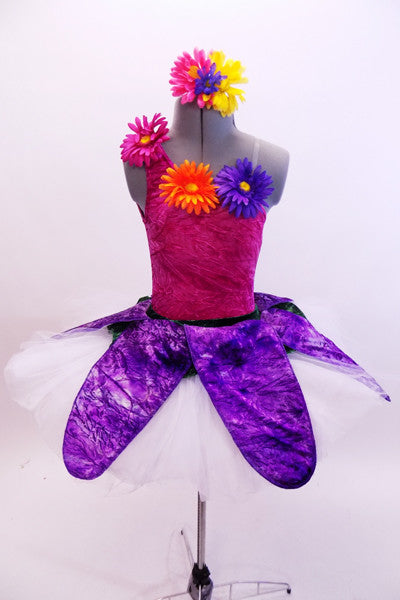 Magenta crushed velvet, one shoulder leotard, has colourful gerbera daisies along bodice & shoulder. Pull-on,white tutu has purple petal overlay with flowers. Matching hair accessory. Front
