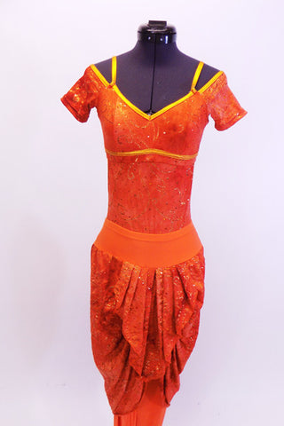 Cap sleeved leotard has open lower back  and low scoop neck with bra-like closure. The orange and gold swirl marble print is accented by gold shoulder straps and piping accent. The matching harem pant has attached pleated draping at both front and back. Comes with matching hair accessory Front