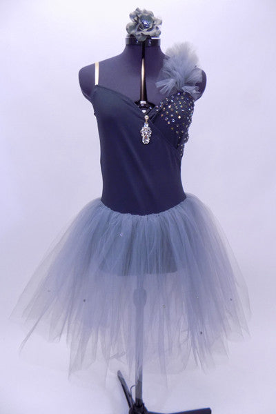 Grey cross over leotard dress has crystals on the left bust & long tulle skirt. There is a large drop crystal accent at the front. Comes with hair accessory. Front