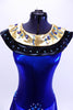 Electric blue halter leotard dress has attached Egyptian style gold and black, jewel/crystal covered collar . There are also jewels and Swarovski crystals at front and sides of waistline. Dress has an open back, attached box skirt and large gold sequined applique at lower back. Front zoomed