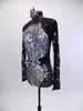 Long sleeved leotard has lace back and sleeves. The brief portion is silver with a black mesh overlay. The front of the leotard is covered in iridescent sequins and has a large jeweled belt which snaps at the back. Comes with a silver and black hair accessory. Side