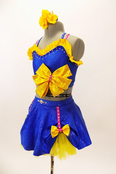 Blue bra top with yellow ruffle & large bow accent. The matching skirt is a blue overlay with  of yellow  petticoat & bows accents. Has floral hair accessory. Side