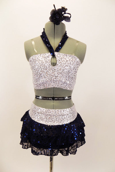 White & silver sequin bandeau bra top has front loop with navy halter collar. The briefs are separate from navy sequined lace skirt. Comes with hair accessory. Front